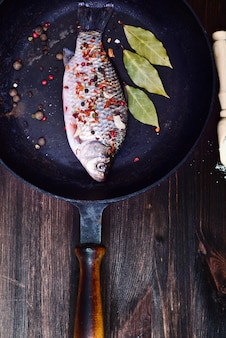 Fischen sie karpfen in gewürzen auf einer schwarzen gusseisenbratpfanne