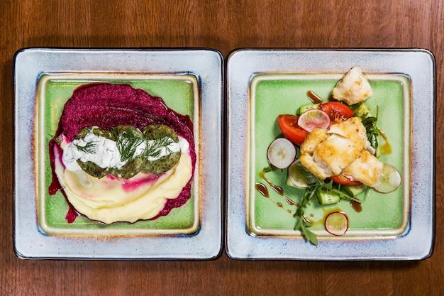 Fischen sie mit gemüse und soßen in den quadratischen platten auf holztisch im luxusrestaurant