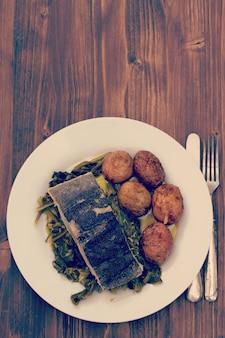Fischen sie mit kartoffel und gemüse auf weißer platte und glas wasser auf braun