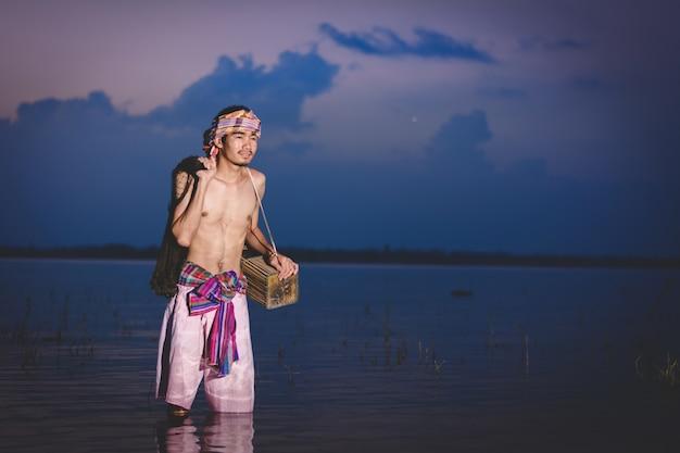 Fischenmann benutzen bambusfischfalle, um fische im see bei sonnenuntergang zu fangen