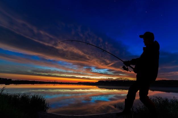 Fischer-angelrute im morgengrauen auf dem see.