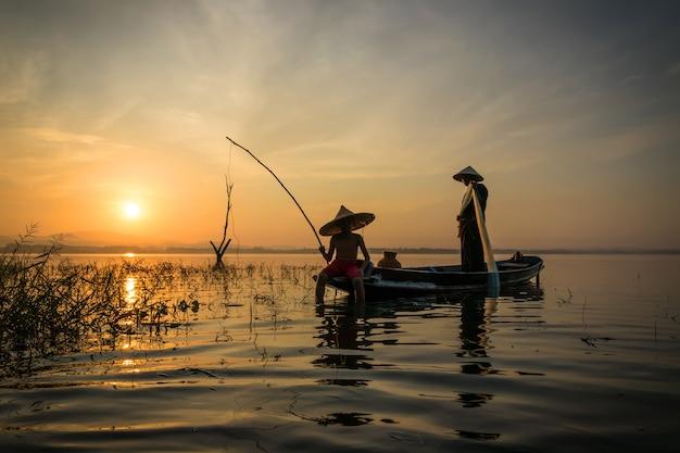 Fischer angelrute mit haken geht früh morgens mit holzboa fischen