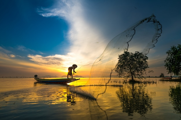 Fischer auf anziehenden fischen des bootes mit sonnenaufgang