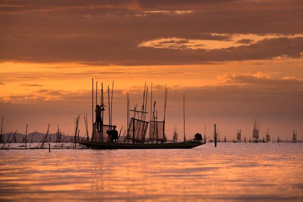 Fischer auf anziehenden fischen des bootes mit sonnenuntergang