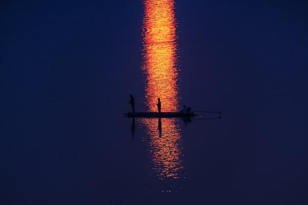 Fischer auf dem boot, das in see, in schattenbild schwimmt und reflektieren sonnenlicht
