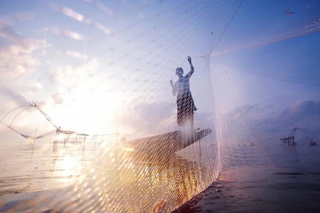 Fischer auf dem bootsfischen mit einem großen fischnetz. silhouettenszene des morgens.