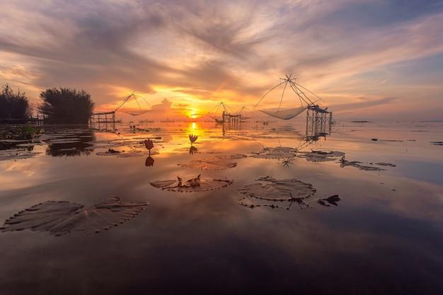 Fischer auf dem longtail-boot am morgen und riesiges quadratisches tauchnetz im dorf pakpra
