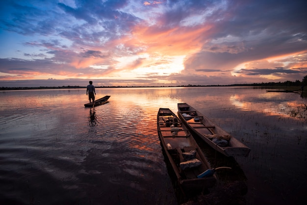 Fischer auf fischerbootschattenbildsonnenuntergang oder -sonnenaufgang im schönen himmel des flusssees