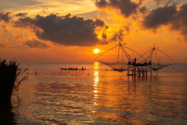 Fischer auf quadratischem badnetz und tourismusboot an pakora-dorf, phatthalung-provinz, thailand