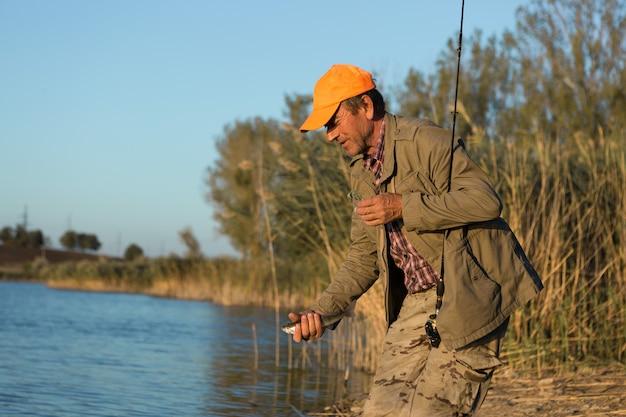 Fischer, der am flussufer steht und versucht, einen fisch zu fangen. sport, erholung, lifestyle.