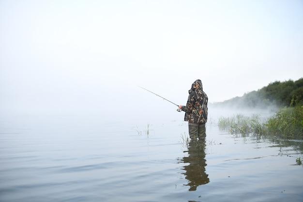 Fischer, der angelrute auf dem see im nebel hält