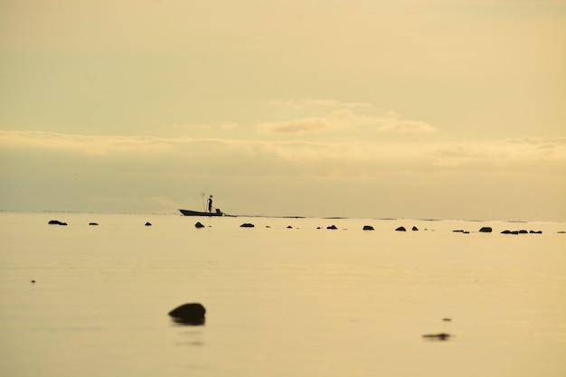 Fischer, der auf boot auf meer steht