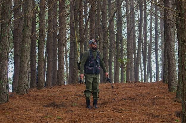 Fischer, der im kiefernwald geht