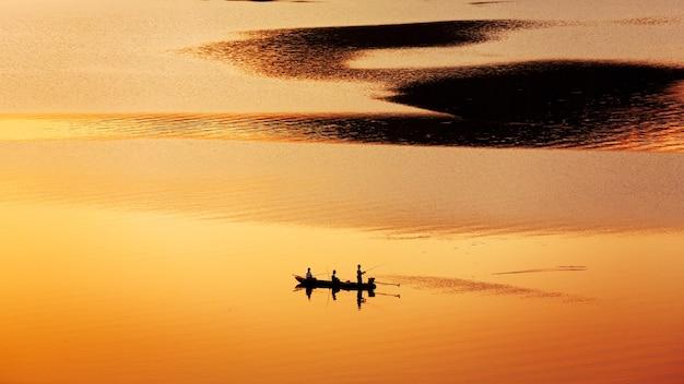 Fischer, der vom boot auf dem see bei sonnenuntergang fischt