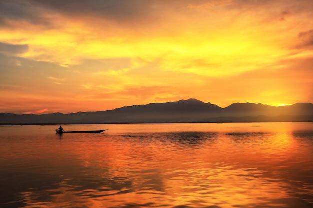 Fischer, die auf dem boot in den sonnenuntergangseen, thailand fischen