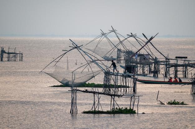 Fischer, die fisch auf quadratischem tauchnetz bei pakpra, phatthalung, thailand fangen