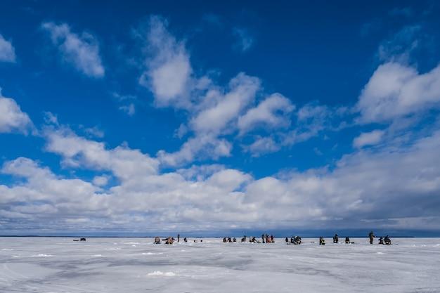 Fischer, die fische im winter auf dem eis an einem tag fangen