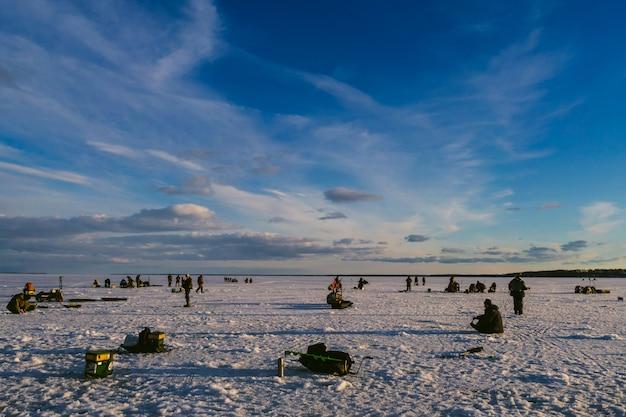 Fischer, die im winter auf dem eis fischen