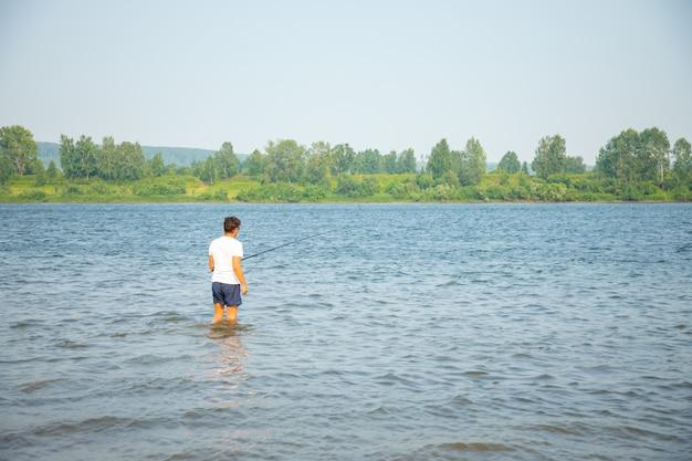 Fischer fängt fische, die im wasser des flusses tom in kemerowo, sibirien, russland stehen