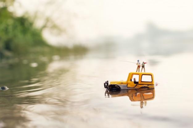 Fischer hält eine angelrute zum fangen von fischen (miniatur, spielzeugmodell)