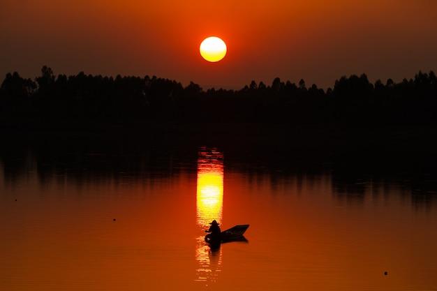 Fischer in aktion beim angeln im see.
