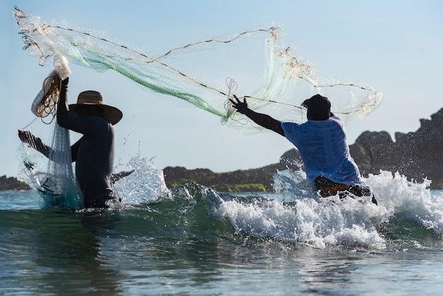 Fischer in aktion werfen fischernetze ins meer mit starken wellen an der küste