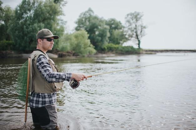 Fischer in der sonnenbrille steht im wasser. er schaut nach rechts. der typ hat ein fischernetz auf dem rücken. mann hält fliegenrute mit einer hand. er sieht ruhig und cool aus.