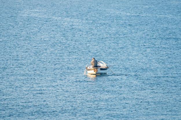 Fischer in einem boot, das am frühen morgen fischt. mittelmeer. italien.