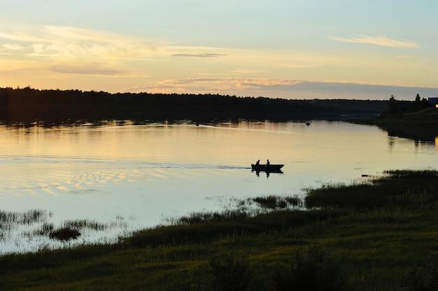 Fischer in einem boot, das fische im fluss fängt