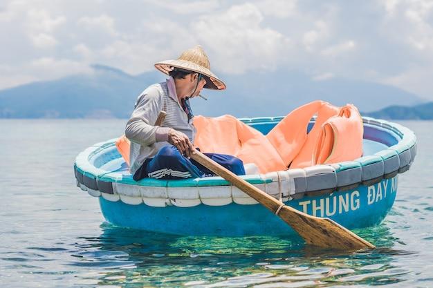 Fischer in einem vietnamesischen boot wie korb.