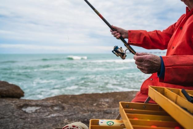 Fischer mit angelausrüstung box.