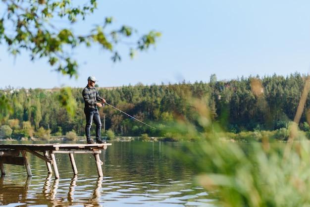 Fischer mit rute, spinnrolle am flussufer