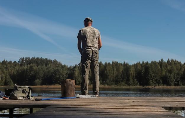 Fischer om holzdock oder pier, der fische auf der reel rod fängt, die im sommer am flussufer steht