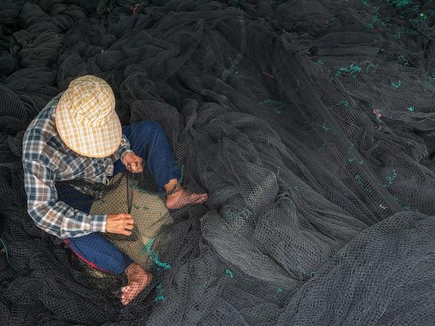 Fischer reparieren fischernetze, ein lokaler fischer am hafen, der netze repariert