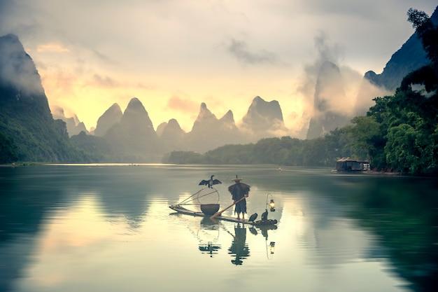 Fischer und fischadler angeln am fluss. in der ferne sind wolken und berge