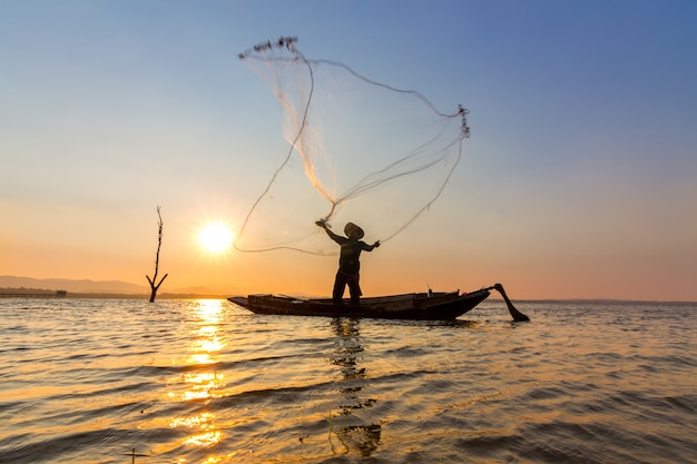 Fischer warf am morgen netz in das wasser