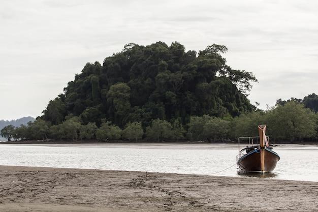 Fischerboot am strand mit dem grünen gebirgshintergrund