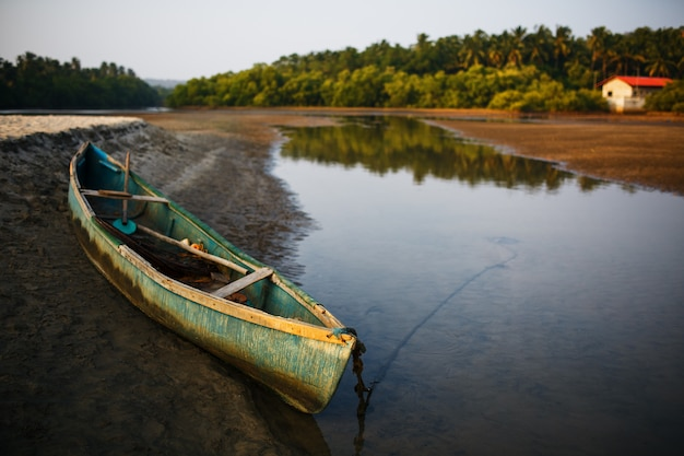 Fischerboot am ufer des flusses in den tropen mit palmen am abend,