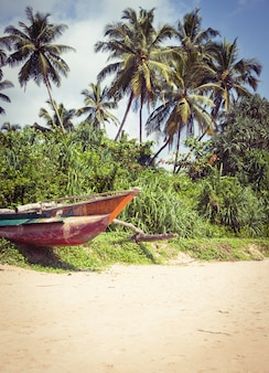 Fischerboot an einem tropischen strand mit palmen