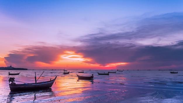 Fischerboot auf dem strand bei sonnenuntergang.