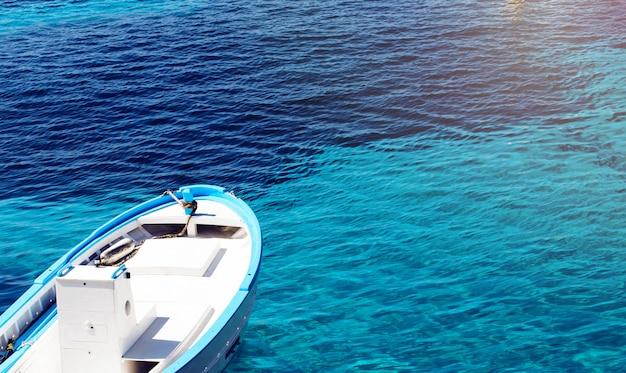 Fischerboot auf einem klaren blauen wasser an einem sonnigen tag. abstrakter hintergrund mit exemplarplatz.