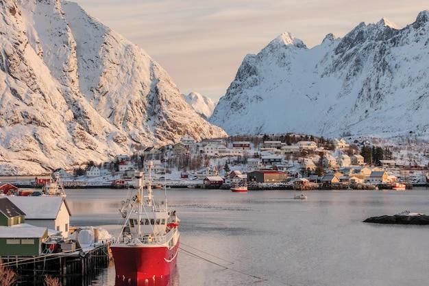 Fischerboot auf pier mit skandinavischem dorf auf lofoten-insel