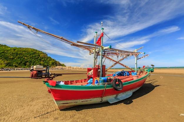 Fischerboot auf sandstrand mit blauem himmel