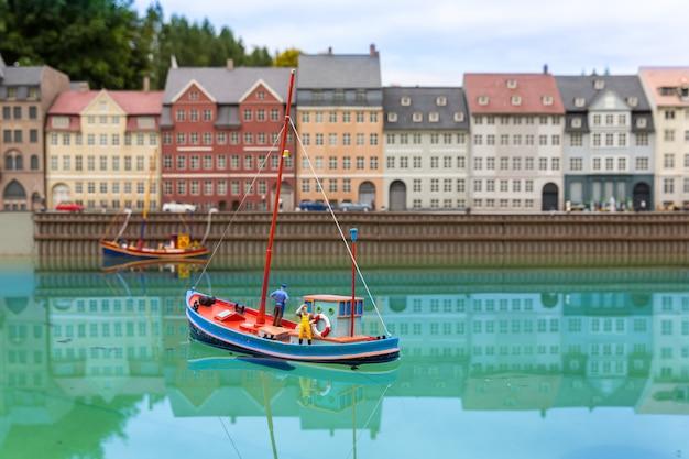 Fischerboot auf stadtfluss, miniaturszene im freien, europa. mini-figuren mit hoher entkalkung von objekten, realistisches diorama