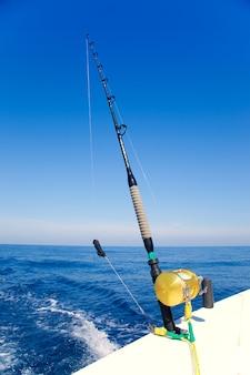 Fischerboot, das im ozean mit goldener spule schleppt