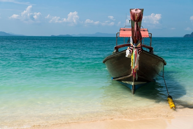 Fischerboot liegt am strand einer tropischen insel.