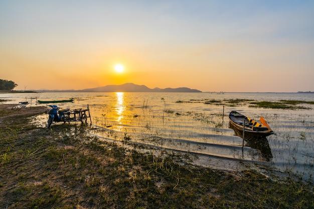 Fischerboot mit sonnenuntergang am bang phra reservoir