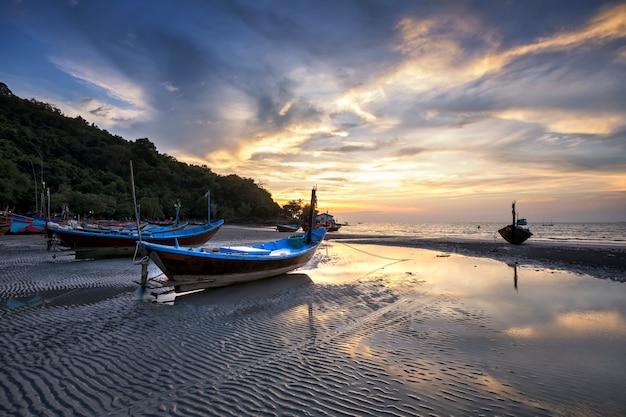 Fischerboot und sonnenuntergang am strand.