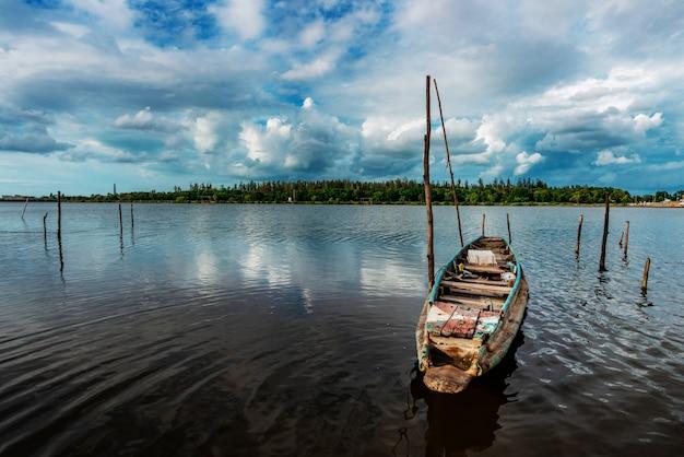 Fischerboot und wasserbarriere und fluss mit wolkenhimmelsturm