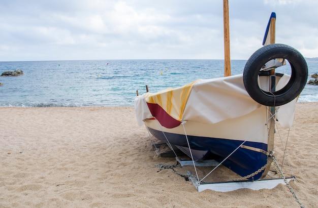 Fischerbootbogen auf blauem himmel und meeresstrandhintergrund. strand mit einem boot nahe der küste von lloret de mar in einem schönen sommertag und mittelmeer auf hintergrund, costa brava, katalonien, spanien.